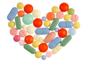 Heart shape made from pills isolated on white