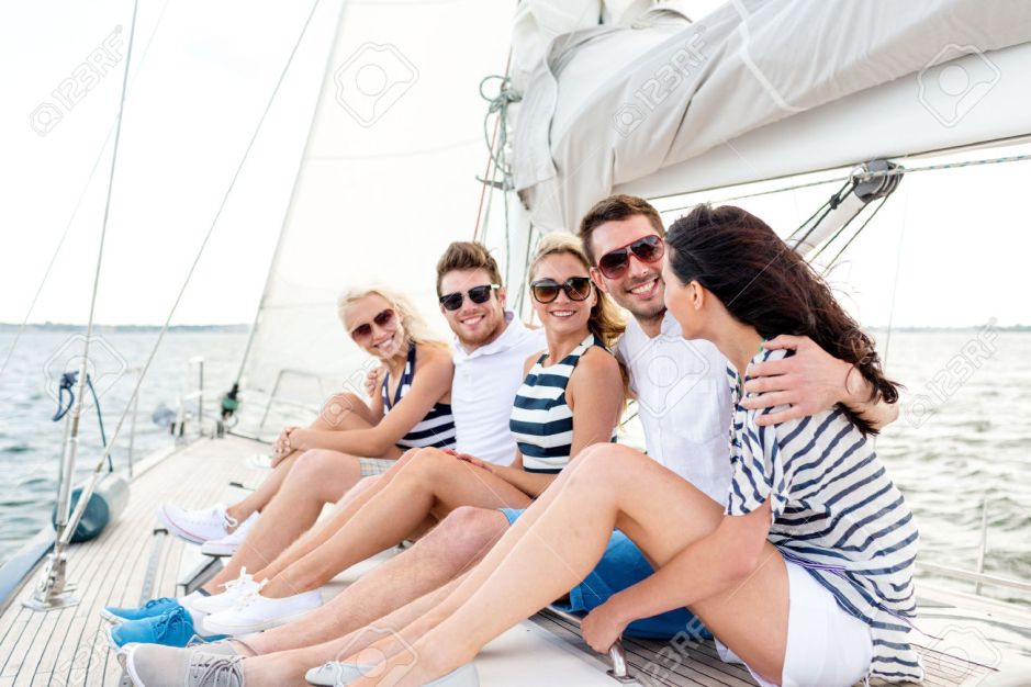 32336913-vacation-travel-sea-friendship-and-people-concept-smiling-friends-sitting-on-yacht-deck-Stock-Photo